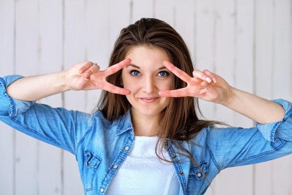 Portret młodej kobiety, uśmiechniętej.
