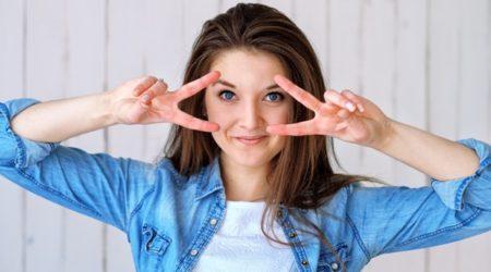 Młoda kobieta, uśmiechnięta. Rozszerza palce u obu dłoni, żeby uwidatnić twarz.